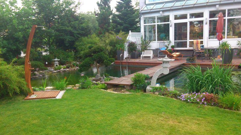 Über die Schwimmteichbrücke vom Garten zur Terasse