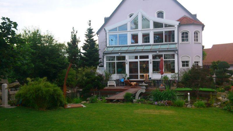Haus, Schwimmteich, Garten in der Abenddämmerung