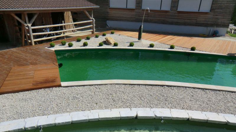 Schwimmteich mit Gartendusche umrahmt mit Kies und Holz